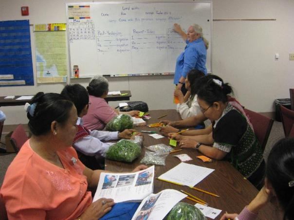Ladies in ESL class with donated bags of fresh spinach.